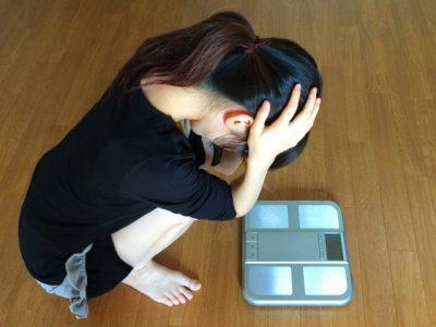 体重計の上で悩む女性