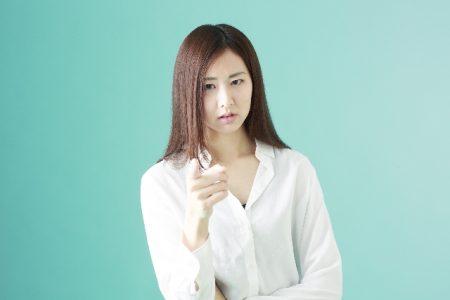 指を差して指摘している女性