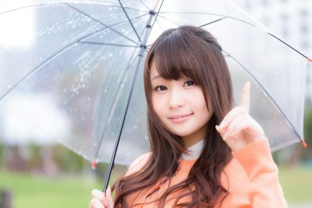 傘を差しポイントを教える女性