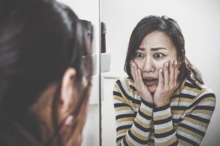 鏡を見て驚く女性